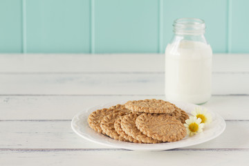 Some cereals cookies, a school milk bottle and a apple