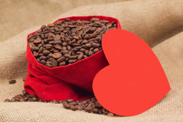 Red paper heart next to velvet red sac with coffee beans