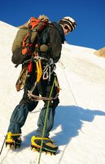 Alpine climber balances on the ice snowfield