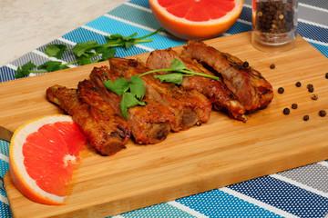 Свиные  ребрышки и красный грейпфрут на разделочной доске