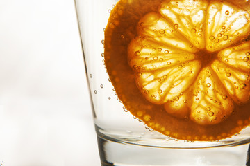 Orange slice in the glass with bubbles
