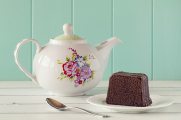 A brownie on a plate. A teapot and a spoon on a white table.