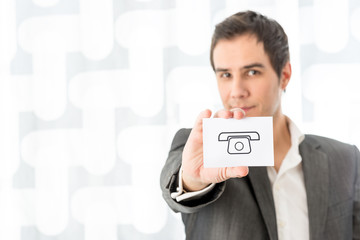 Businessman holding a white card with phone symbol with copyspac