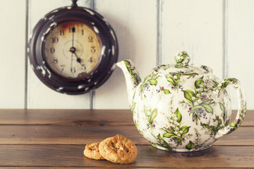 A teapot, cookies and a clock. Five o'clock. Tea time. Vintage