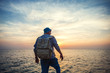 traveler with backpack  looking far away at beautiful sunset