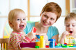 woman playing and teaching with kids - 76910878