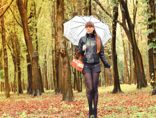 Beautiful woman posing in the rain holding an umbrella in park