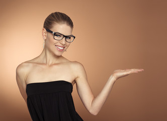 Cute girl in glasses advertising smth, pointing at copy space