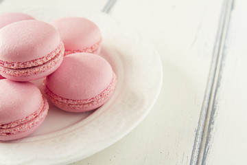 Some macarons (macaroon) on a plate over a white wooden table.