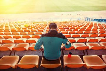 sweaty sportsman sitting on the chairs at stadium