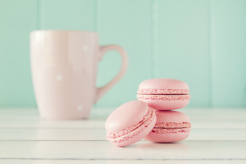 Some macarons (macaroon) and a pink mug. Vintage Style.