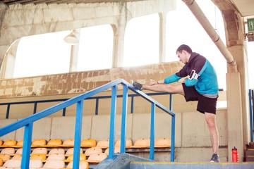 sportsman doing stretching exercise at stadium
