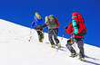 Leinwandbild Motiv Two mountain backpackers walking on snow