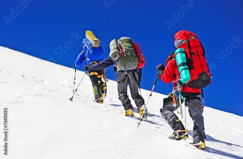 Two mountain backpackers walking on snow - 76911435