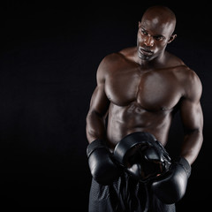 African male boxer against black background