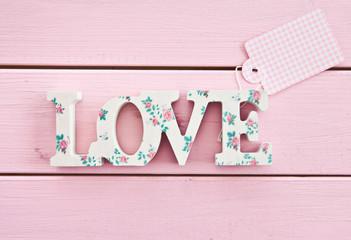 LOVE auf rosa Holzhintergrund