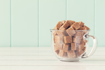 Some brown cane sugar cubes in a glass cup. Vintage Style.