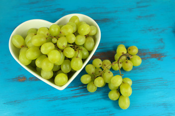 Green grapes in heart shaped bowl on a turquoise wood background