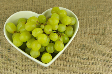 Green grapes in a heart shaped bowl on a rustic background