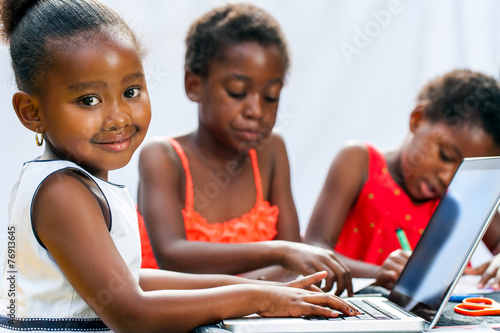 Little African girl doing homework on computer with friends. - 76913645