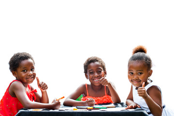 Three African girls doing thumbs up at table.