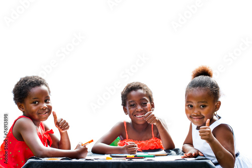 Three African girls doing thumbs up at table. - 76913898
