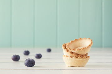 A stack of tartlets and several blueberries. Vintage Style.