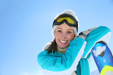 Woman in ski outfit standing at top of mountain