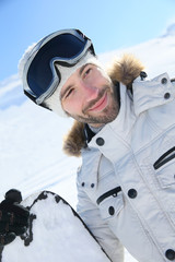 Portrait of cheerful snowboarder at top of ski slope