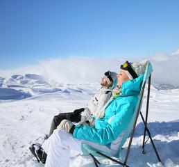 Couple of skiers sunbathing at top of ski slope