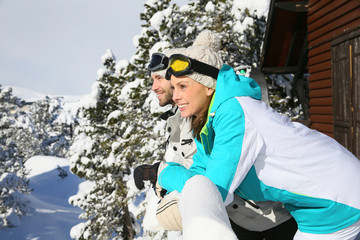 Couple of skiers admiring panorama from log cabin