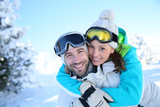 Man giving piggyback ride to girlfriend in snowy mountain