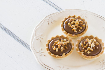 Some tartlets with chocolate on a plate. Vintage Style.