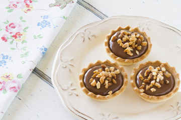 Some tartlets with chocolate on a plate and a napkin. Vintage