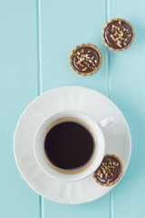 A coffee and tartlets on a robin egg blue wooden table. Vintage