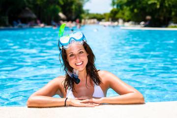 Happy woman swimming in tropical resort pool