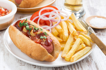 fast food - hot dog with French fries and chips on table
