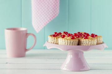 Some vol-au-vent with red currants on a cake stand and a mug