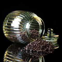 Coffee beans spilling out vintage glass jar on black background