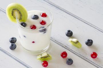 A healthy breakfast: yogurt, blueberries, kiwi and red currants.