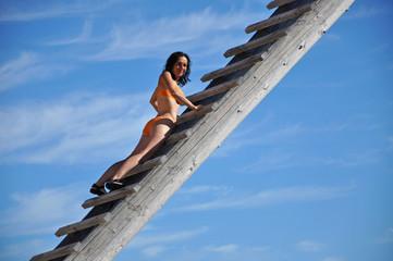 Woman climbing up a wooden ladder