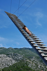 Sexy woman sunbathing on a wooden ladder