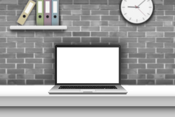 Laptop with blank screen on desk in office interior.