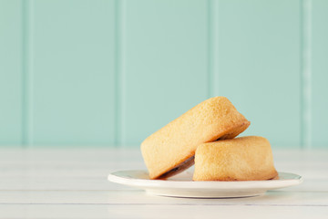 Two twinkies on a white wooden table. Vintage Style.