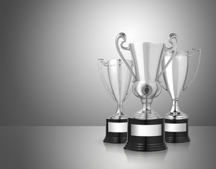 silver trophies on gray background