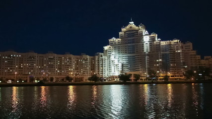 Modern city building on river embankment at night