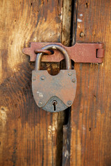 The padlock on an old wooden door