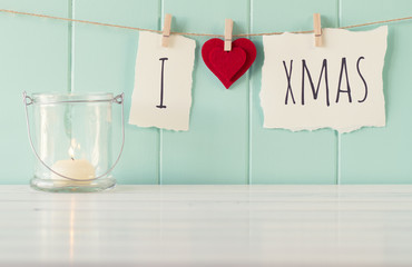 """""""I love xmas"""" hanging on a rope with clothespins."""