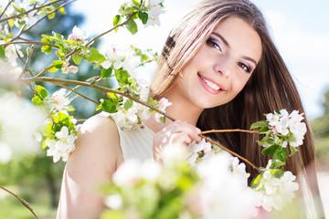 Beautiful girl in a cherry blossom garden