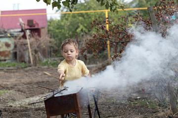 Boy making fire in a grill